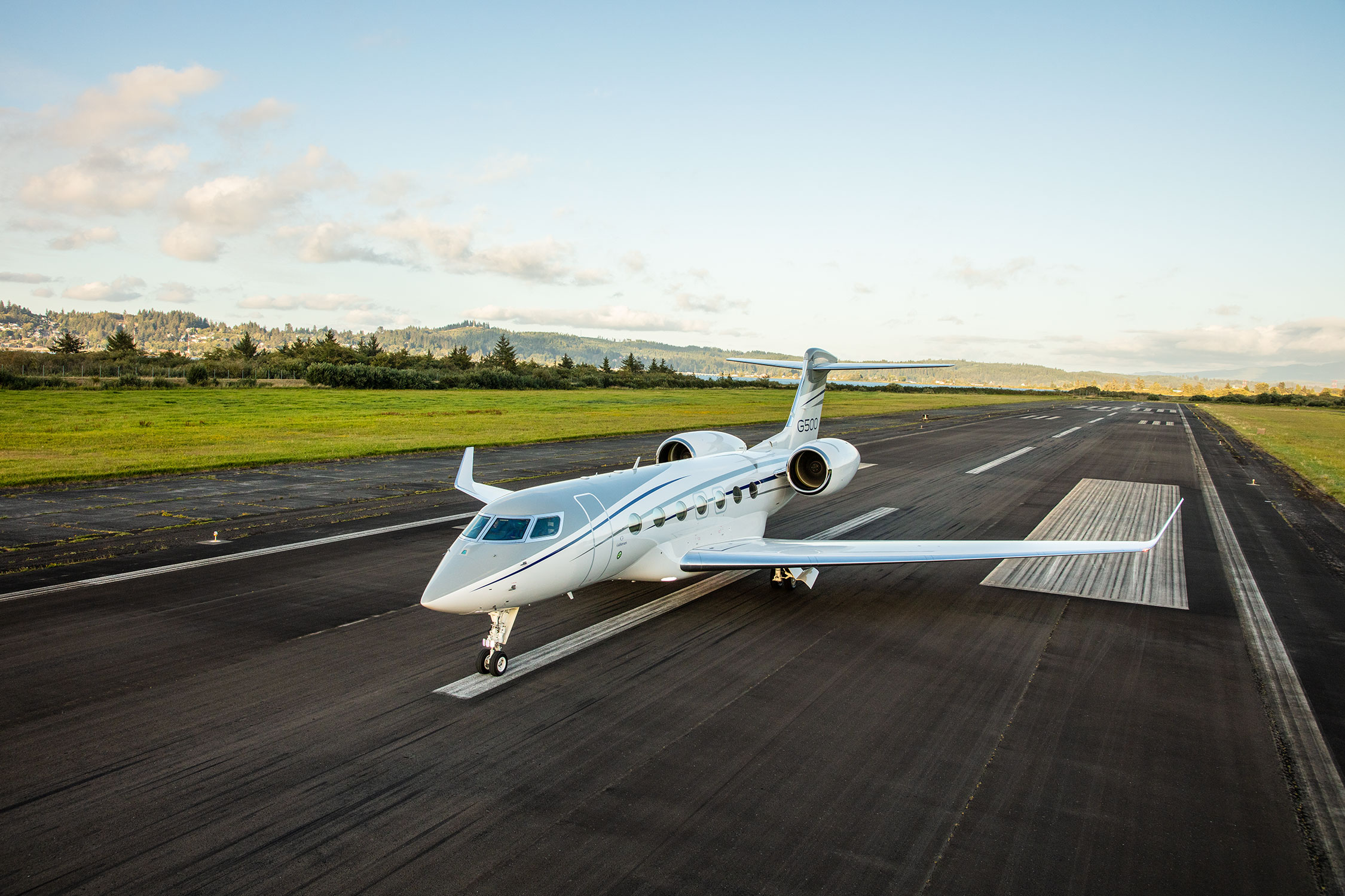 G500 aircraft parked on runway with green fields and trees in the distance