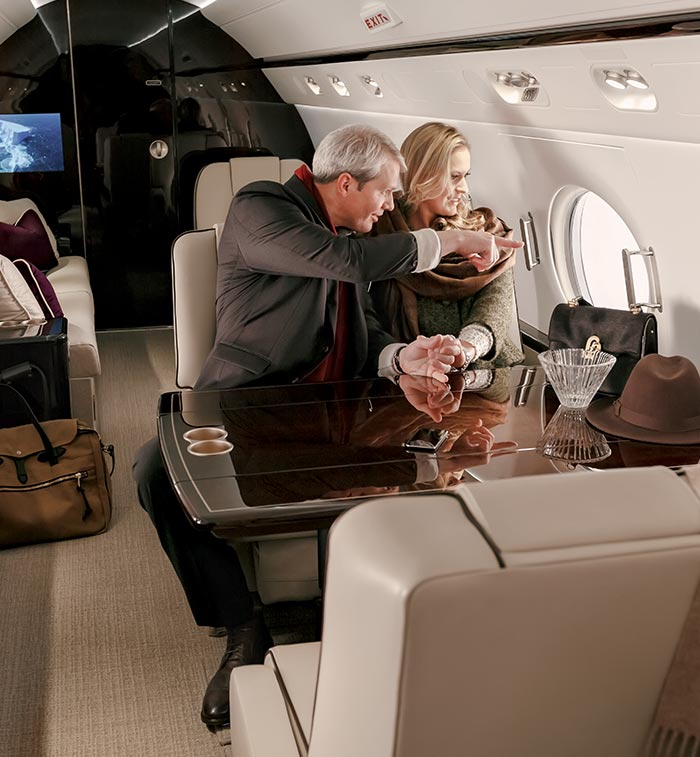 A man and woman staring out the window from their private aircraft