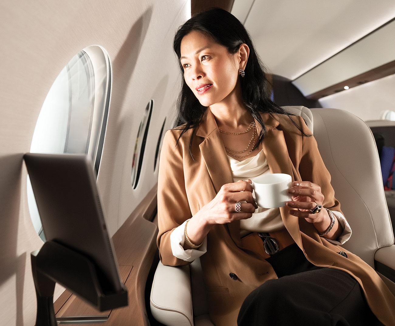Women enjoys hot beverage in leather chair while gazing out aircraft window