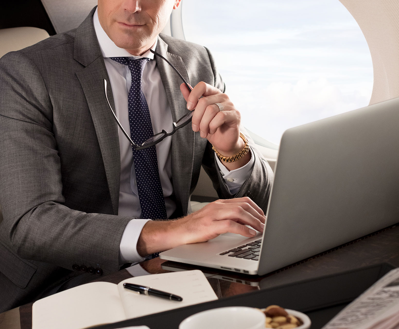 Man with glasses working on computer inside G500 aircraft