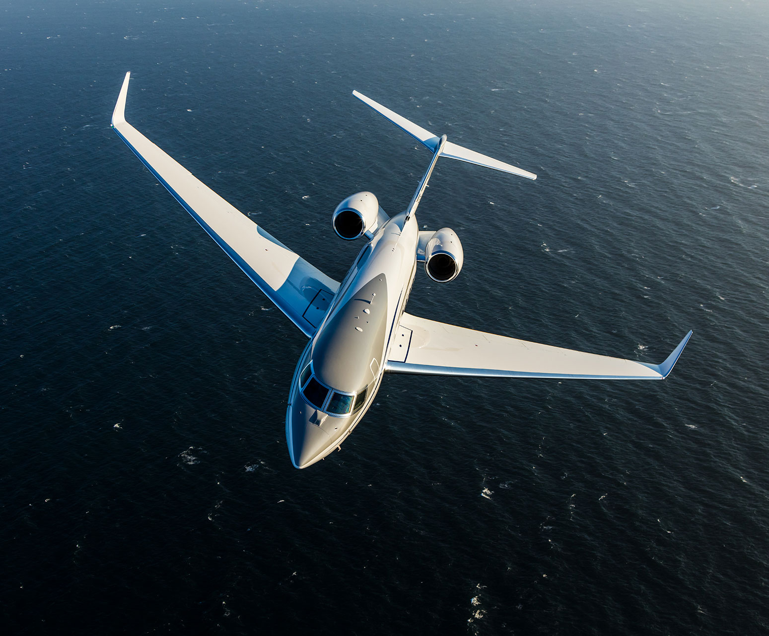 Gulfstream G650ER flying over water.