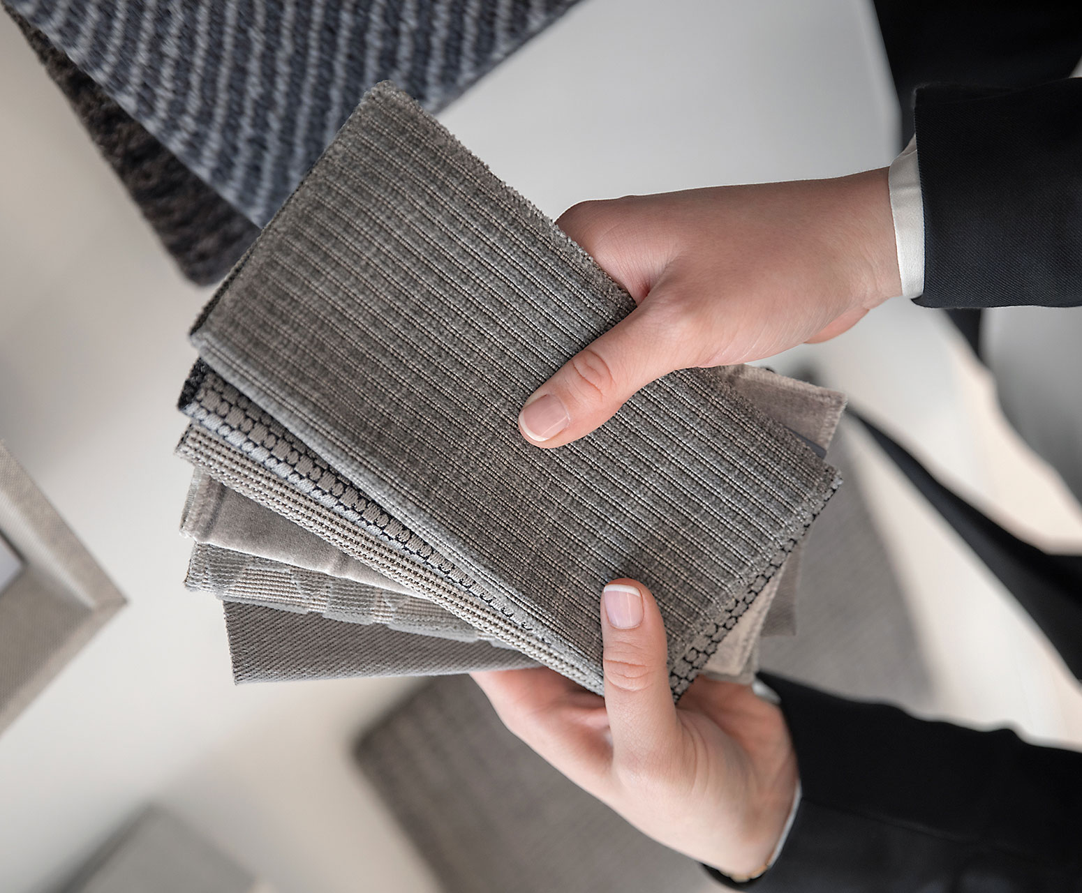 A pair of hands touching fabric samples.