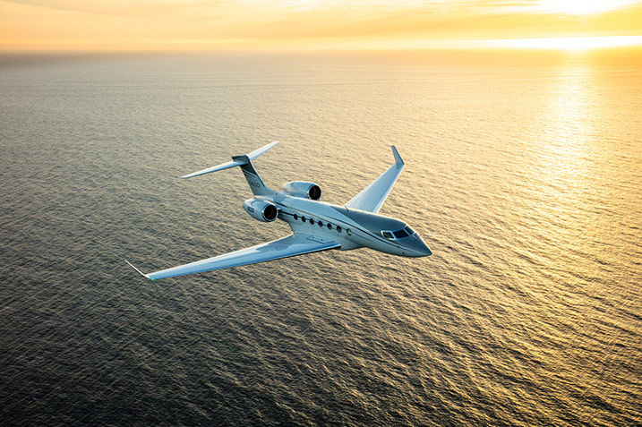 G600 Flying Over Water at Sunset